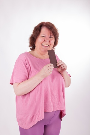 A fat woman with a bar of chocolate in her hand photo