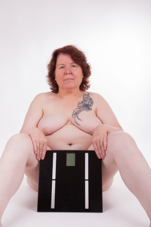 A fat woman is shocked about her weight Stock Photo