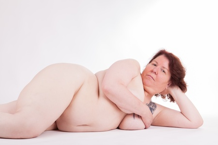 A fat nude woman is lying  in front of the camera