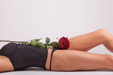 A red rose is lying on a beautiful girl