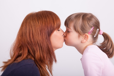 A young mother is kissing her daughter