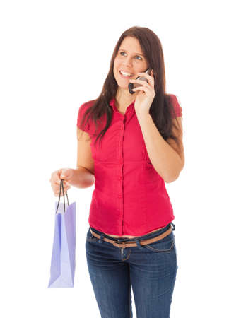 The young girl is telephoning with a shopping bag in her hand Stock Photo - 15896130