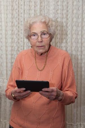 An old woman with a tablet computer photo