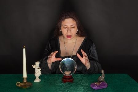 ocultismo: Una mujer morena vestida est� mirando en una bola de cristal Foto de archivo