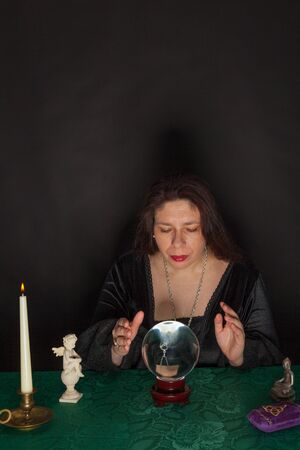 interpret: A dark dressed woman is looking into a crystal ball