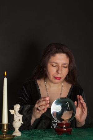 A dark dressed woman is looking into a crystal ball