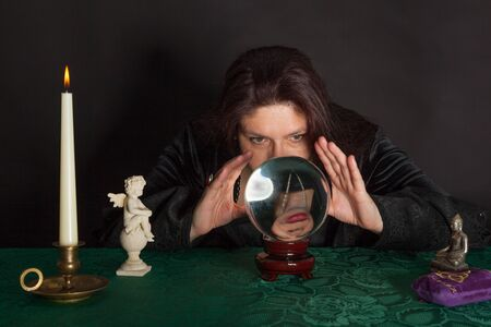 A dark dressed woman is looking into a crystal ball Stock Photo - 16331410