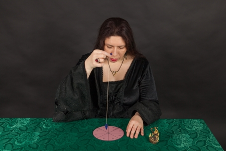 A dark dressed woman is working with a pendulum
