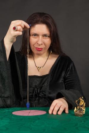 esot�risme: Une femme brune habill�e travaille avec un pendule