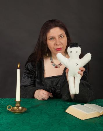 esot�risme: Une femme brune habill�e est poignard� une poup�e avec une aiguille Banque d'images
