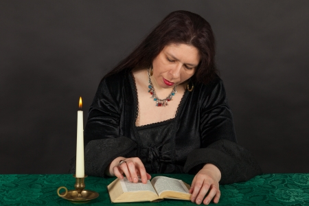 bewitchment: A dark dressed woman is reading a book Stock Photo