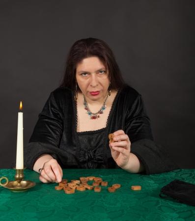esoterismo: Una mujer morena vestida est� diciendo el futuro con runas Foto de archivo