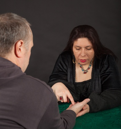 bewitchment: A dark dressed woman is doing a palm reading