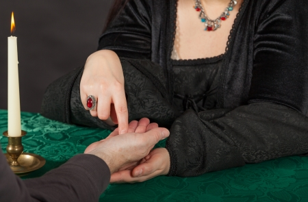 esoterismo: Una mujer morena vestida está haciendo una lectura de la palma