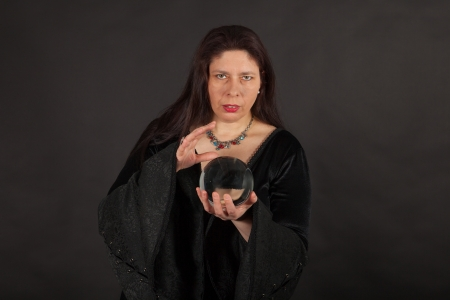 A dark dressed woman is looking into a crystal ball Stock Photo - 16326313
