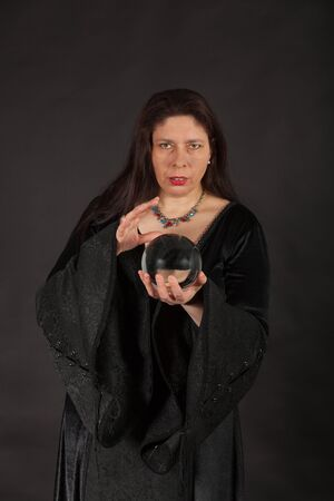 esoterismo: Una mujer morena vestida está mirando en una bola de cristal Foto de archivo