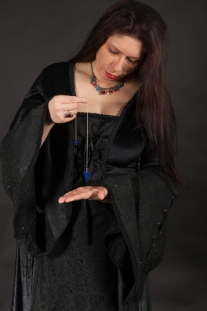 A dark dressed woman is working with a pendulum photo