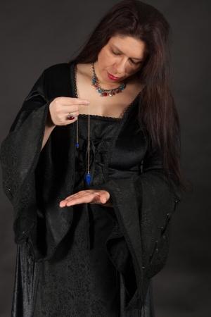 esoterismo: Una mujer morena vestida est� trabajando con un p�ndulo