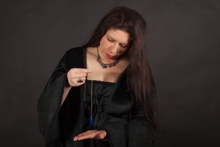 A dark dressed woman is working with a pendulum Stock Photo - 16326367