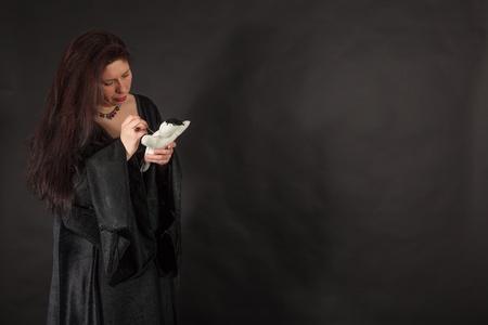 esoterismo: Una mujer morena vestida está apuñalando a una muñeca con una aguja
