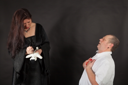 A dark dressed woman is stabbing a doll with a needle photo