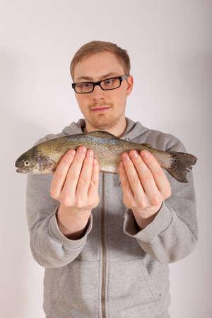 A young man has a fish in his hand Stock Photo - 17565739