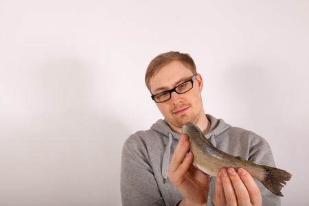 A young man has a fish in his hand Stock Photo - 17565747