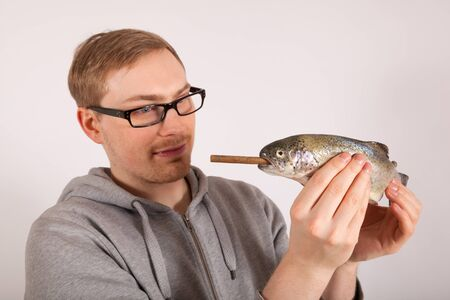 A young man has a fish in his hand Stock Photo - 17565734