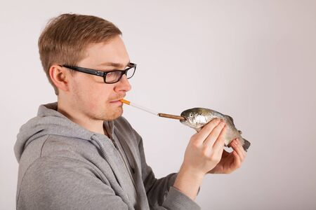 A young man has a fish in his hand photo