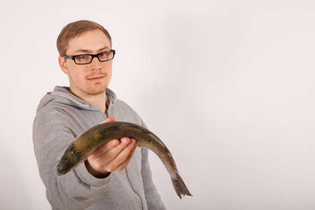 A young man has a fish in his hand Stock Photo - 17565738