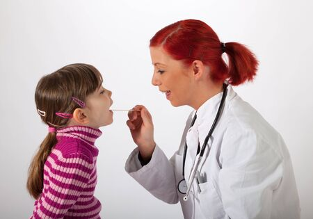 The young pediatrician looks a little girl in the mouth Stock Photo - 17797583
