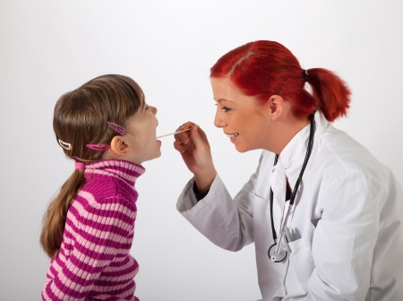 The young pediatrician looks a little girl in the mouth Stock Photo
