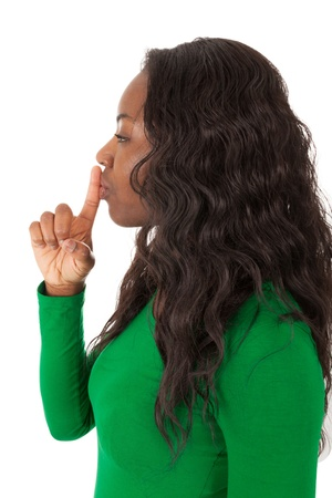 The young colored girl has a finger in front of the mouth Stock Photo - 18205327