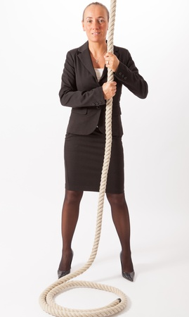 The young woman is climbing up a thick rope Stock Photo - 18343644