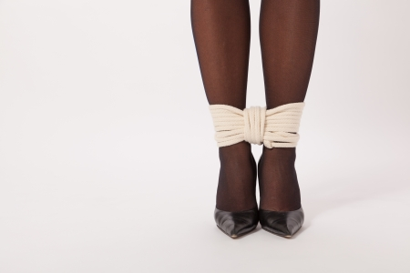 The feet of a young woman are tied with a rope Stock Photo - 18343662