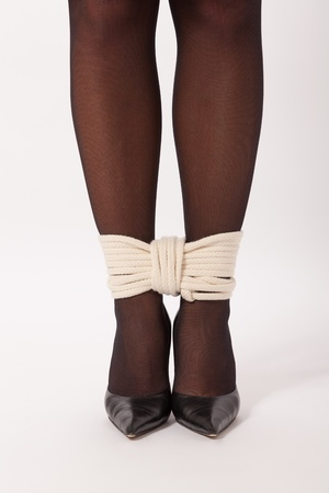 The feet of a young woman are tied with a rope photo