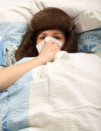 The young girl is lying sick in bed and blowing her nose photo