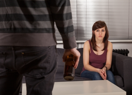 The man is standing with a bottle of beer in front of his girlfriend