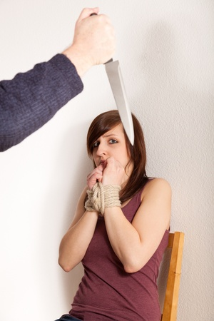 The angry father is threatening his daughter with a knife photo