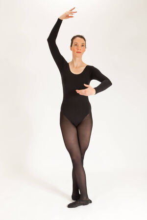 The young ballet dancer is standing in front of the camera