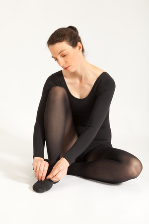 The young ballet dancer is sitting in front of the camera