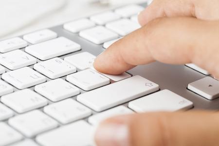 Woman Hand pushing keyboard button photo