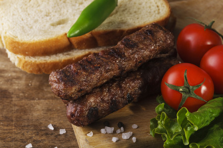 Kebapche (Cevapcici) with vegetables and bread on wooden board photo