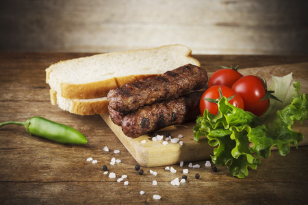 balkan: Kebapche (Cevapcici) with vegetables and bread on wooden board Stock Photo