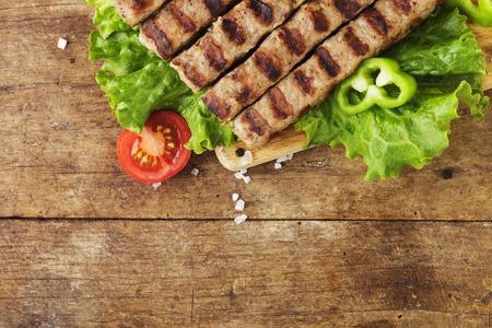 Kebapche mit Gemüse und Brot auf Holzbrett Standard-Bild - 33455152