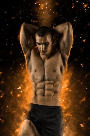 Hombre atlético sexy mostrando six pack abs en negro con fuego Foto de archivo - 57854447