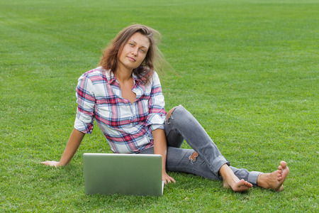 Young woman with laptop sitting on green grass and working outside