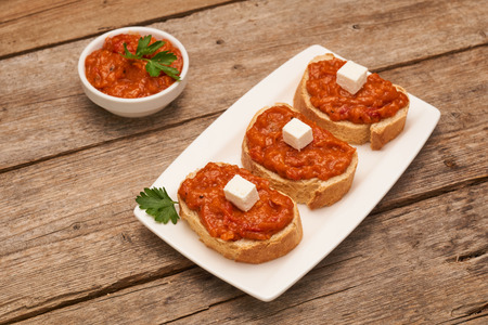 Roasted pepper dip on bread whit feta cheese on wooden board