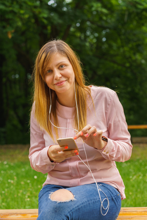 smiley face car: Young woman texting on smart phone outdoors Stock Photo