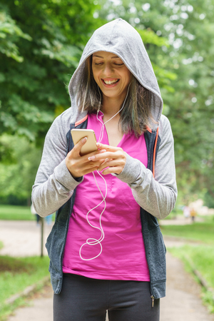 smiley face car: Young fitness woman texting on smart phone outdoors Stock Photo